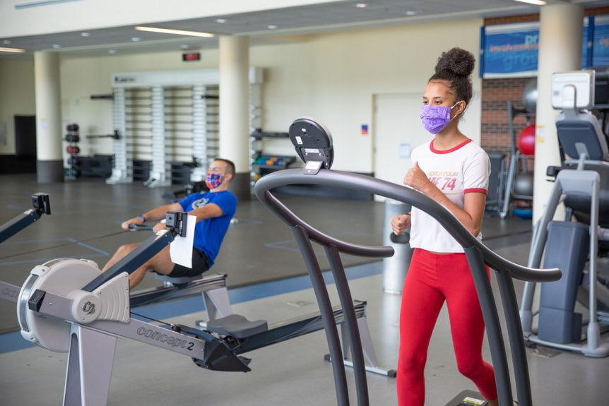 A person wearing a mask and running on a treadmill