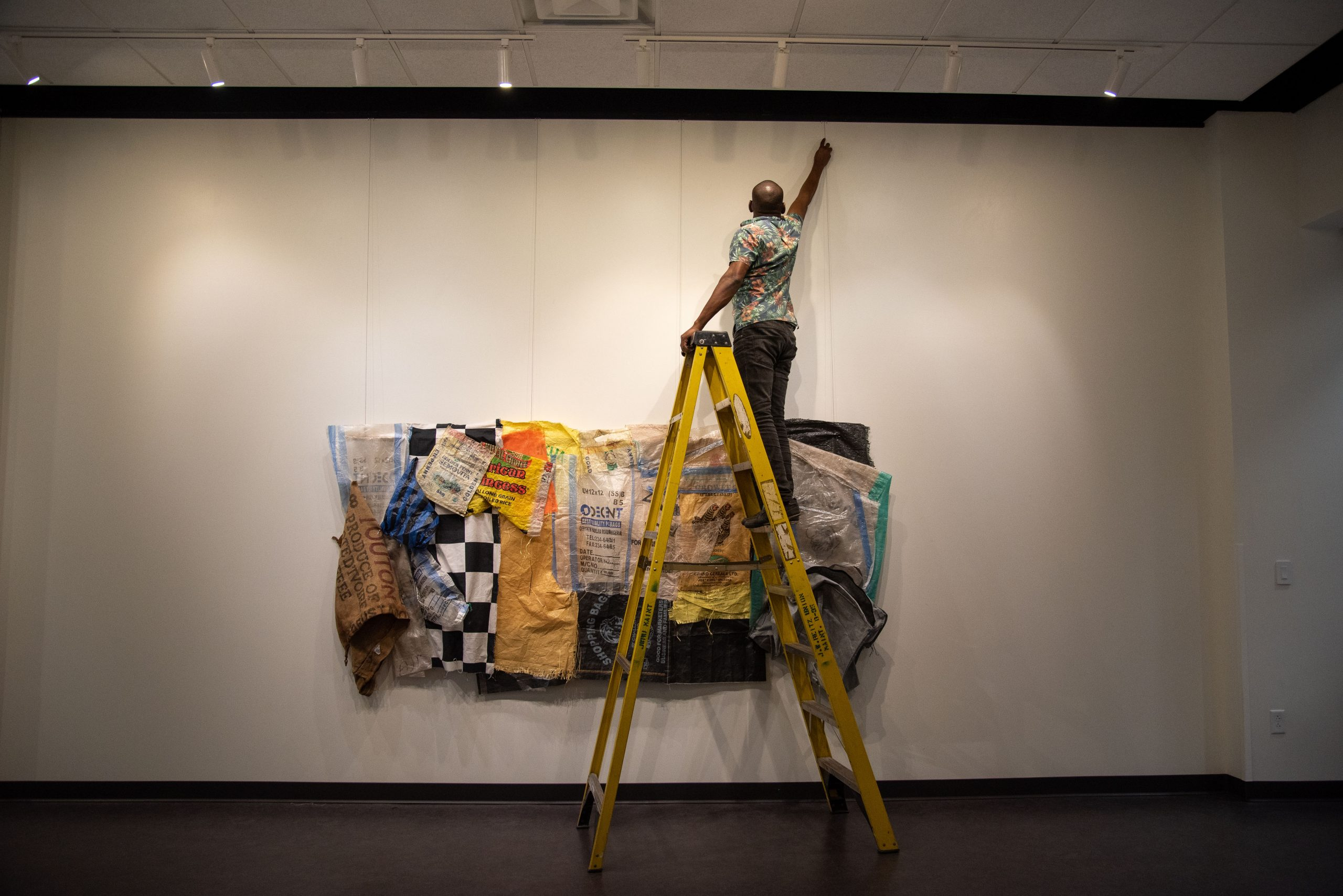 An artist hanging a painting