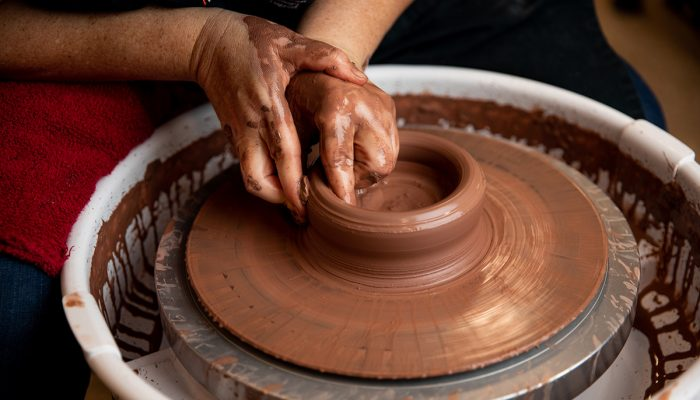 Close up of hand shaping clay